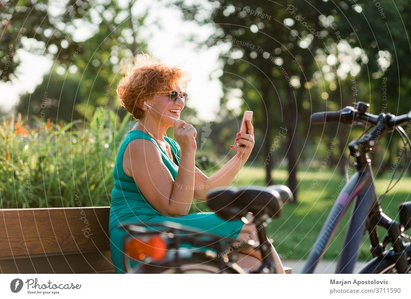 Mature woman using video call on her smartphone in the park 60s age aged app bench bike caucasian cheerful communication connectivity earphones elderly enjoying