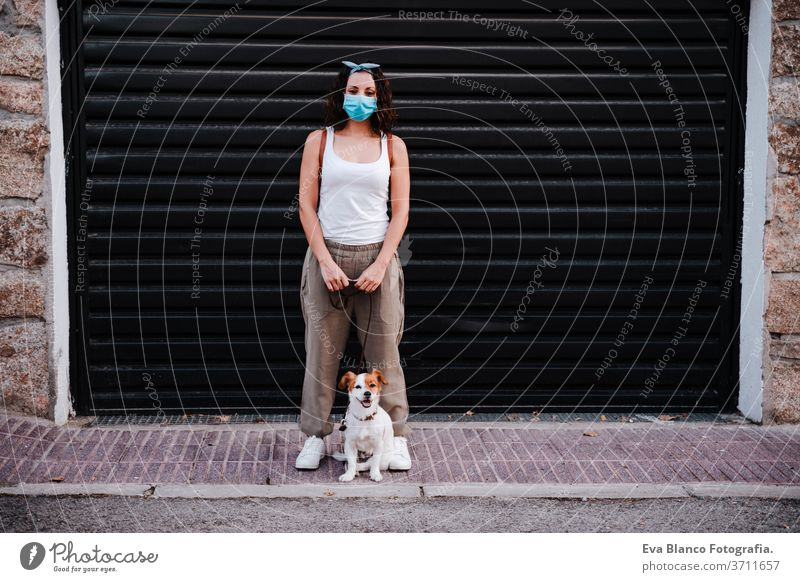 young woman outdoors wearing protective mask, cute jack russell dog besides. New normal concept street new normal pet walking urban city lifestyle corona virus