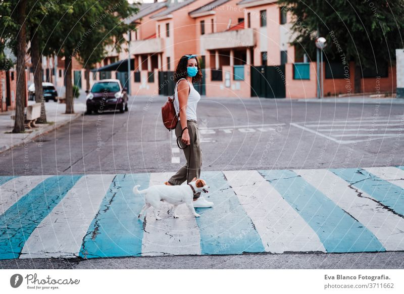 young woman walking by pedestrian crossing wearing protective mask, cute jack russell dog besides. New normal concept street new normal pet urban city lifestyle