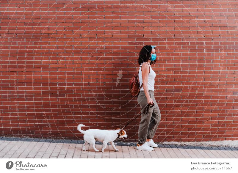young woman walking outdoors wearing protective mask, cute jack russell dog besides. New normal concept street new normal pet urban city lifestyle corona virus