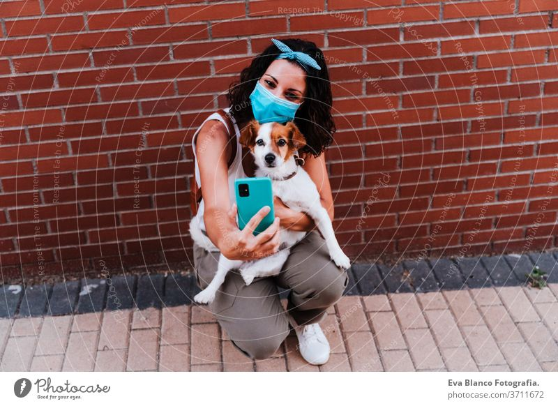 young woman walking outdoors wearing protective mask, taking a picture with mobile phone of cute jack russell dog. New normal concept street new normal pet