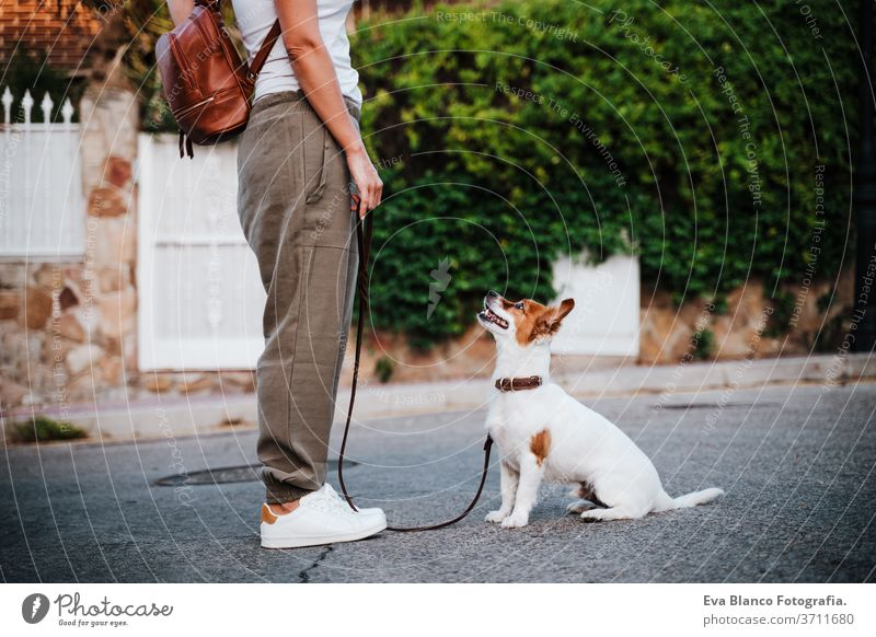 close up of young woman outdoors wearing protective mask, cute jack russell dog besides. New normal concept street new normal pet walking urban city lifestyle