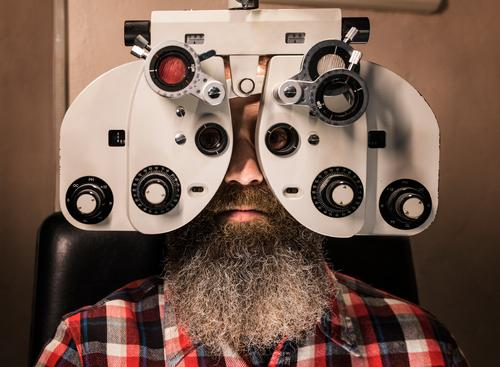 Bearded man performs vision test with phoropter bearded eye glasses 40s 35-39 years adult customer healthy indoors lenses looking at camera male medical men