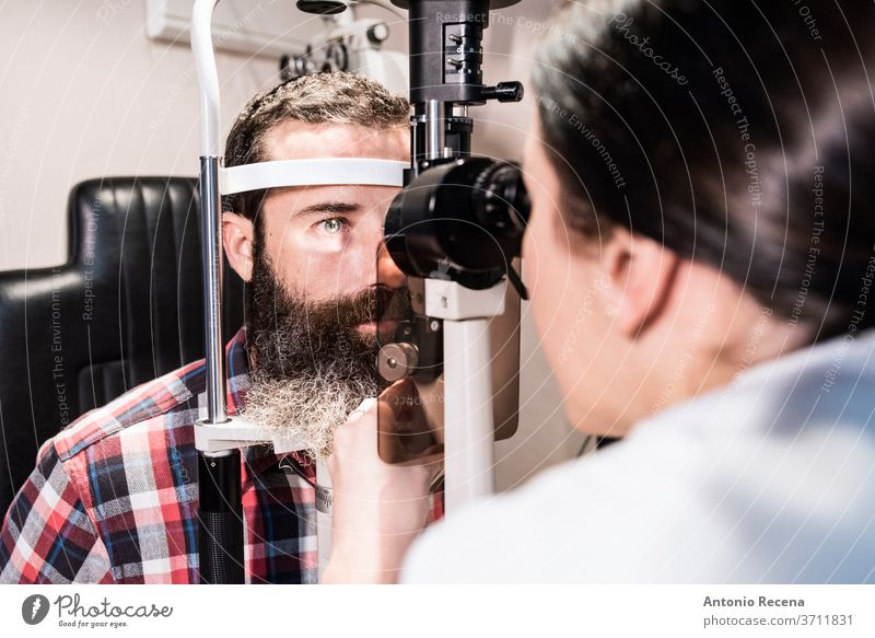 Woman examines the sight of a bearded man in optical center using a slit lamp Slit lamp optics ophthalmology vision test working worker pharmacy person people