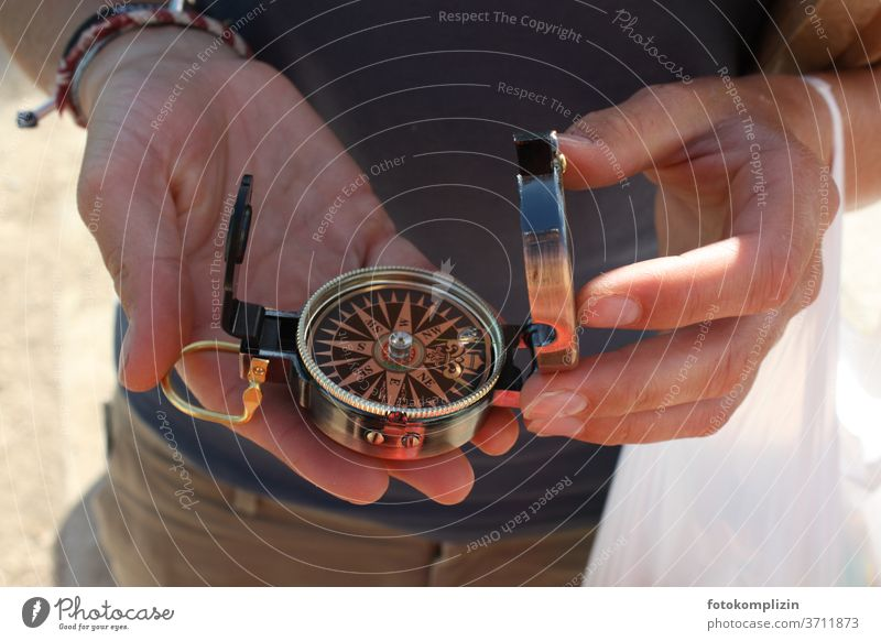 two hands holding a small compass Compass (Navigation) Direction groundbreaking Change in direction Orientation Compass point Road marking Clue Recommendation