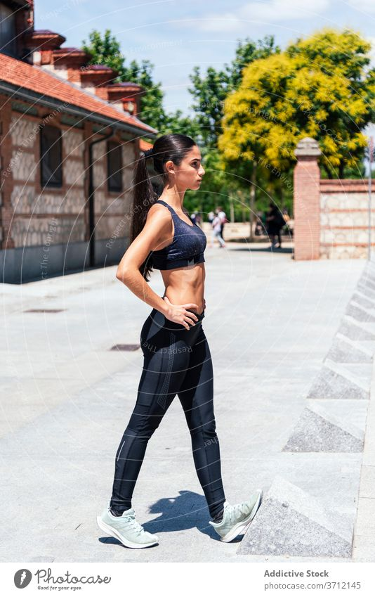 Sporty woman stretching legs on street sportswoman lunge exercise training athlete workout fitness slim young female sportswear wellness wellbeing lifestyle