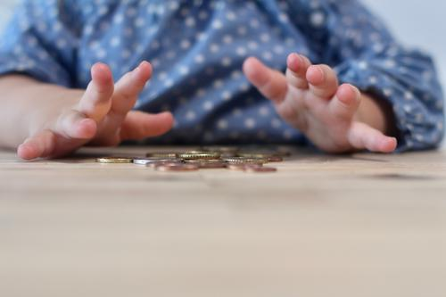 Pocket money. A child plays at a wooden table with coins, cents. Children's Hands Cent Euro Coin game curious explore children's hands Pattern points Money