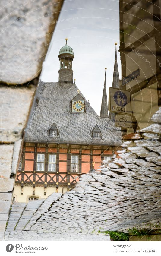 Reflection of the Wernigerode town hall in a puddle of rain reflection Mirror image Puddle Rain puddle Cobblestones rainwater Water Wet Exterior shot