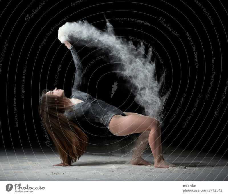 young beautiful woman with long hair is dressed in a sports black bodysuit and sits on the floor and throws white flour over her graceful gymnast up gymnastic
