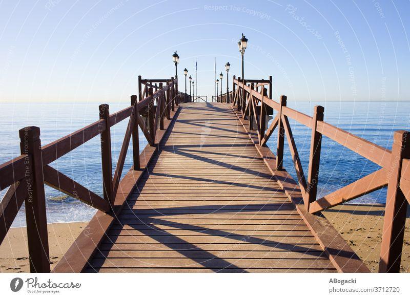 Pier on Costa del Sol in Marbella, Spain pier jetty sea wooden structure costa del sol spain marbella ocean water beach outdoor nature mediterranean sea