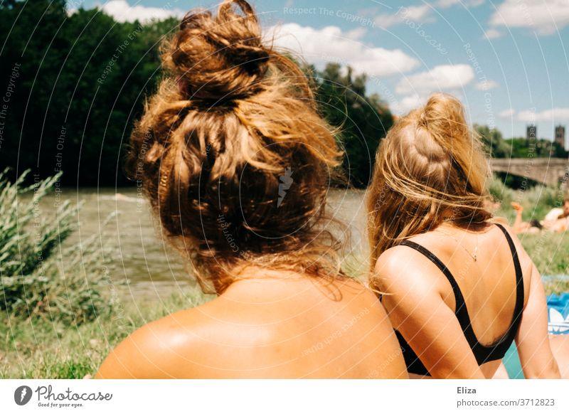 Two young women in bathing suits sunbathing by a river in summer. Summer Young women summer atmosphere Woman Sun River bathe Swimwear Bikini Blonde Girl