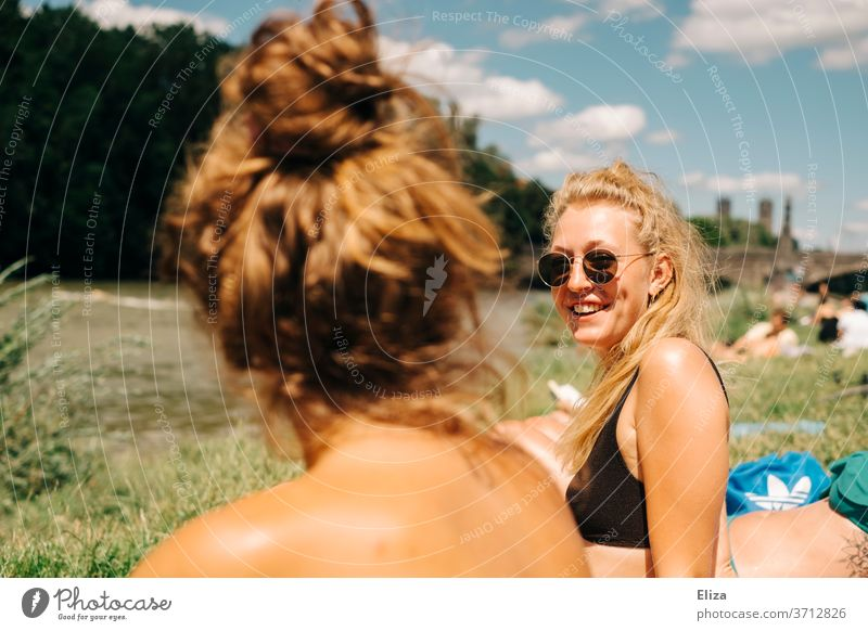 Two young women sunbathing and swimming at the Isar in Munich. One of them is blond, wears sunglasses and laughs. Summer. girlfriends Blonde sunbathe Good mood