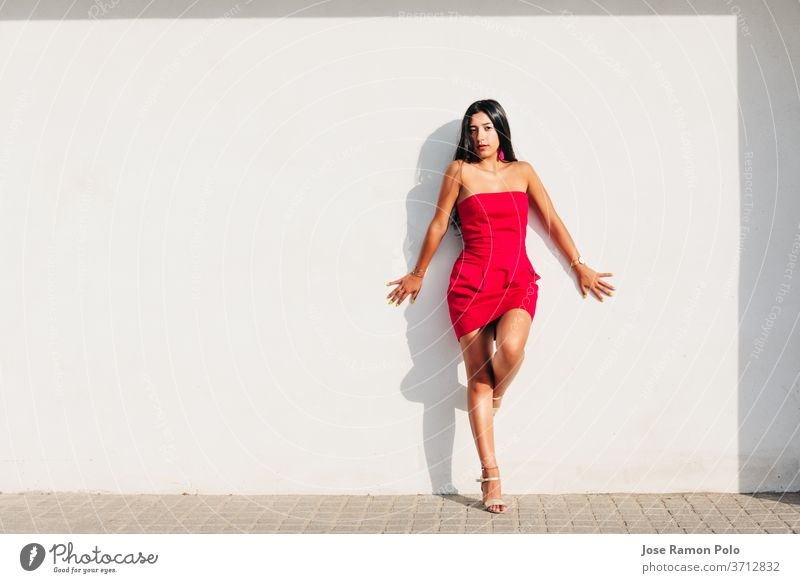 portrait of elegant latin young girl with long brunette hair and red dress on white wall with strong shadow, looking at camera White background beauty