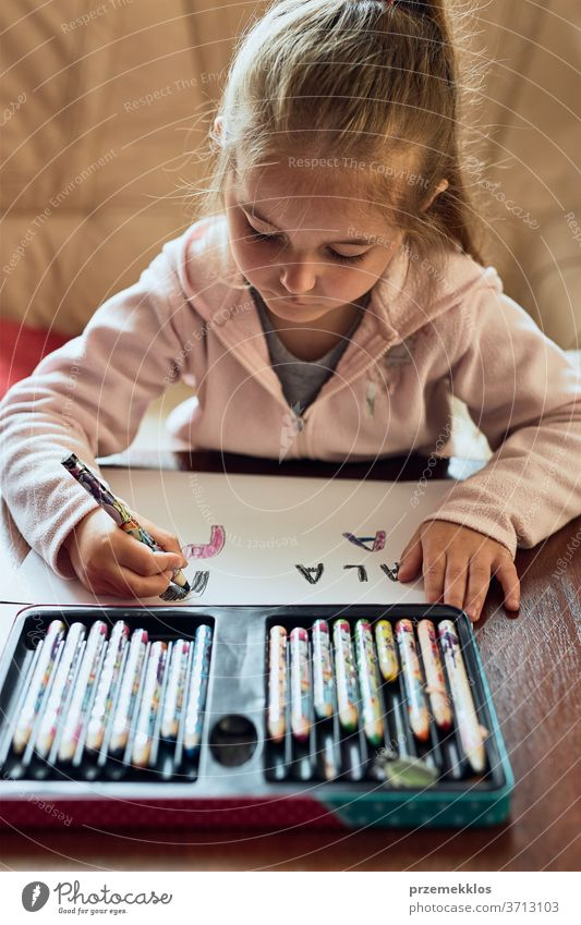 Little girl preschooler learning to write letters at home. Kid using crayons doing homework. Concept of early education attention caucasian child childhood cute