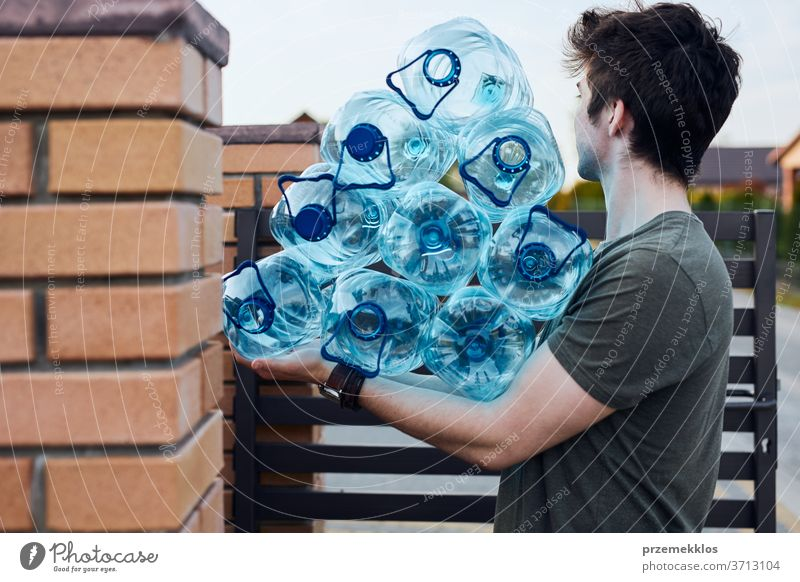 Young man throwing out empty used plastic water bottles into trash bin. Collecting plastic waste to recycling. Concept of plastic pollution and too many plastic waste. Environmental issue