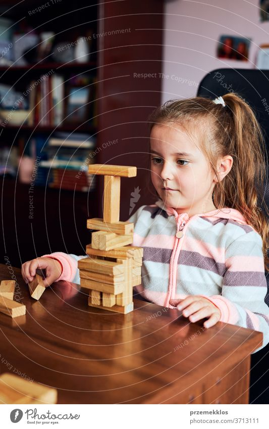 Little girl preschooler playing with wooden blocks toy building a tower. Concept of building a house child biulding brick education game creativity concept