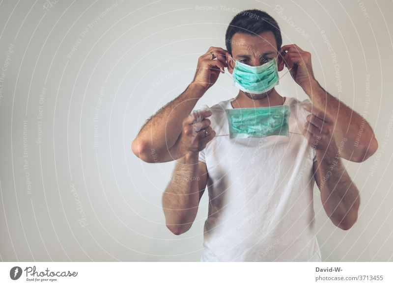 Corona - man puts on a breathing mask / mouth guard correctly Man Mask To put on Correct Testing & Control corona Safety Healthy Mask obligation pandemic