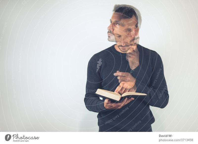 Man holds a book in his hands and looks up something / thinks / thinks Meditative Book books Reading Education Study Library Know School Literature