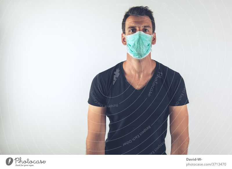 young man with breathing mask looks into the camera corona coronavirus pandemic Respirator mask Mask Authentic real lose patience Virus Illness Healthy