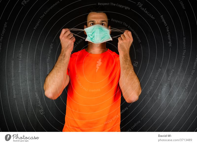 Man holds a mask / mouth guard in front of his face Mask corona Face hands To hold on stop wind Attract To put on test Mask obligation people Human being Duty