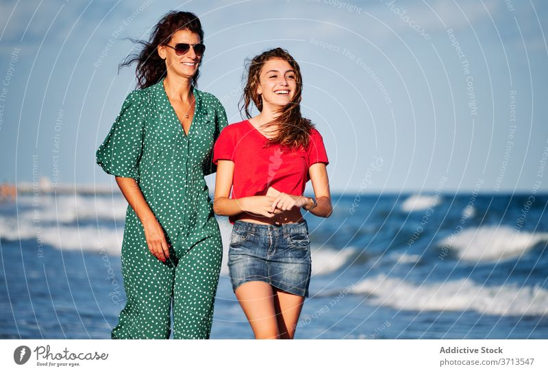 Happy mother and daughter walking along beach sea happy together laugh style summer enjoy female outfit coast lifestyle shore cheerful ocean communicate talk