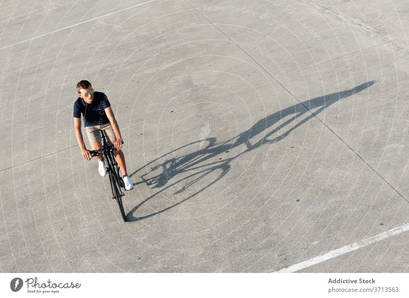 Young man riding bicycle on the street adult bike blond casual caucasian copy space ride cycling cyclist lifestyle male millennial mobility modern people