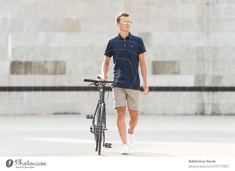 Young man with bicycle on the street adult bike blond casual caucasian copy space ride cycling cyclist lifestyle male millennial mobility modern people riding
