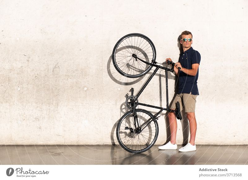 Man carrying his bicycle on concrete wall adult bike blond casual caucasian cycling cyclist lifestyle lean male man hold millennial mobility modern people