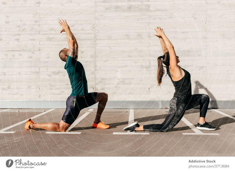 Fit couple doing yoga together in city crescent lunge pose practice asana anjaneyasana sportswear meditate healthy harmony wellness balance stretch flexible