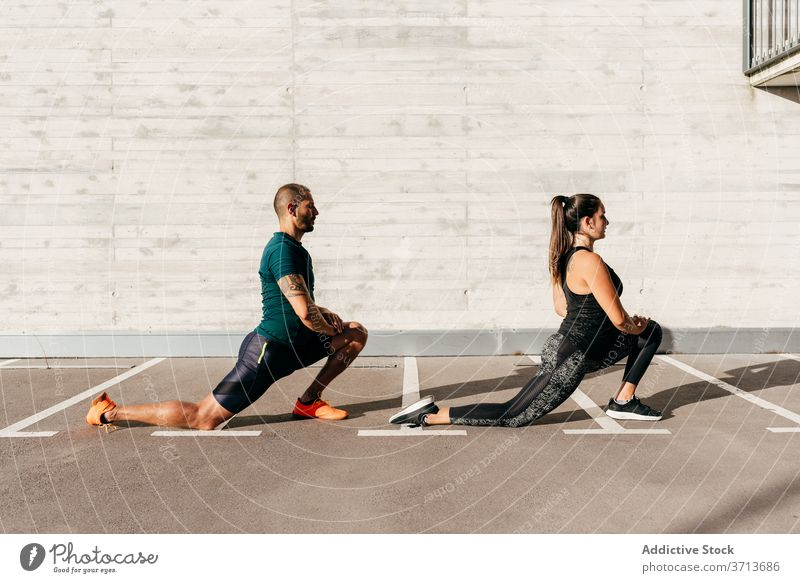 Sportive couple warming up before workout warm up training stretch body together athlete flexible sportswear healthy activity wellbeing stand lunge sportswoman