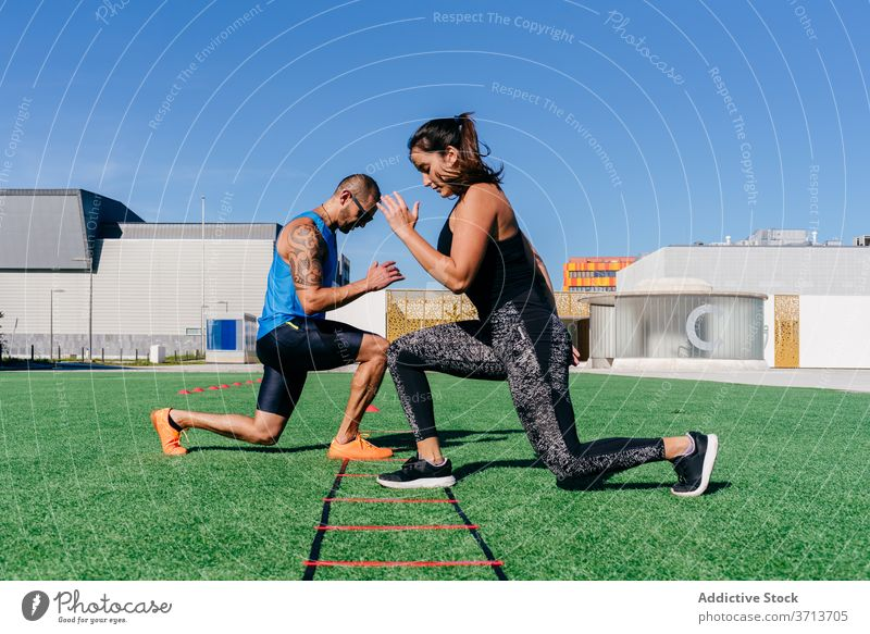 Athletic couple exercising with agility ladder on sports ground athlete training exercise equipment lunge together workout fitness activity sporty energy