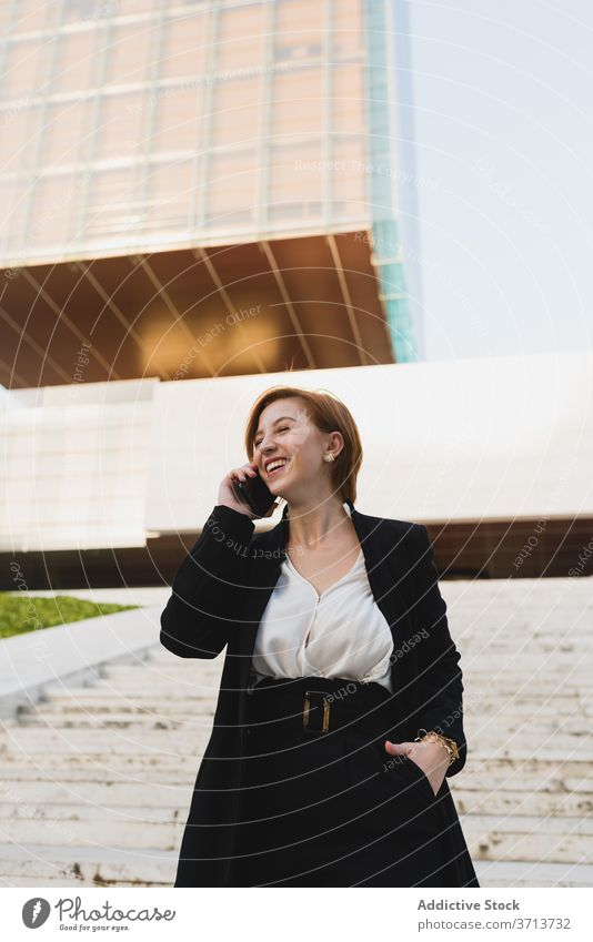 Delighted businesswoman talking on smartphone on street discuss work walk city manager using female chat conversation connection communicate elegant suit
