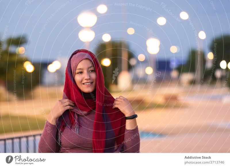 Smiling Arab woman in hijab on street put on muslim religious city evening headdress content female ethnic arab smile happy style glad delight joy relax