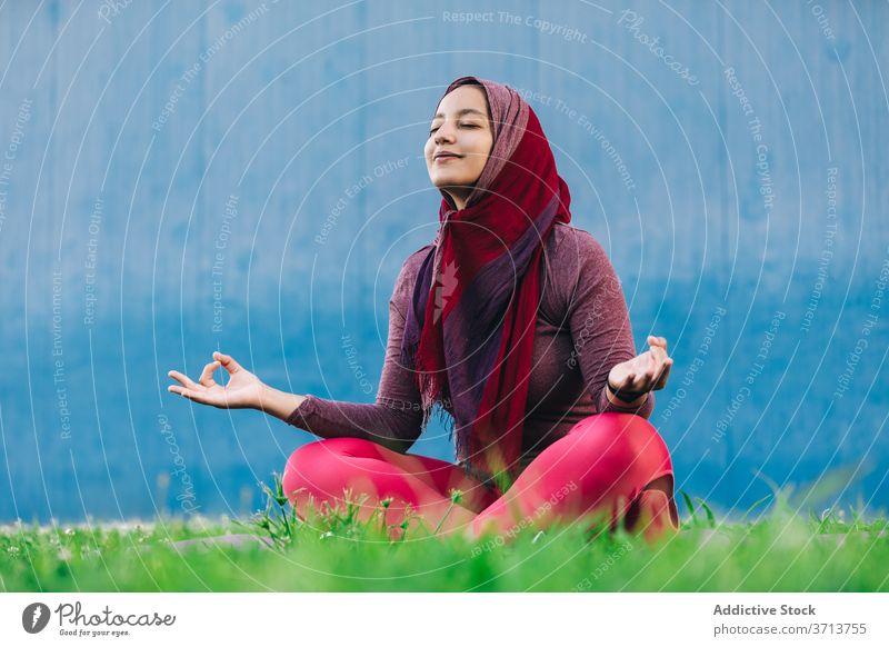 Muslim woman meditating in Lotus pose meditate yoga lotus pose park practice asana mindfulness stress relief padmasana female arab ethnic hijab muslim
