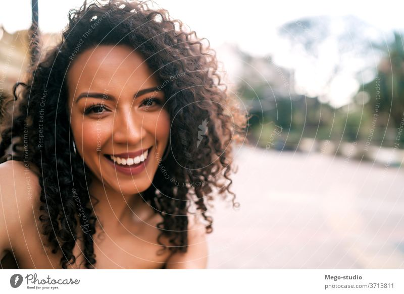 Afro american woman taking a selfie in the city. people afro portrait fun cool smile curly hair style joyful laughing modern outdoor ethnicity stylish cute