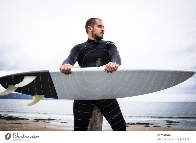 Surfboard Surfer, Man in Mask and Wetsuit on the Beach recreation surfing male sport surfer action athlete extreme hobby ride risky wave weather person