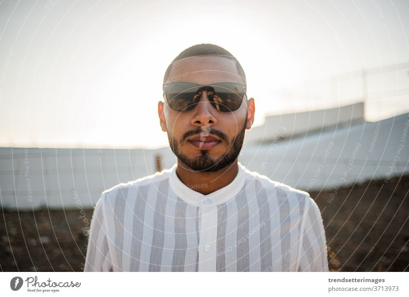 Portrait of a confident and casual man, modern muslim wearing sunglasses entrepreneur moroccan elegant lifestyle fashionable cool hope light success
