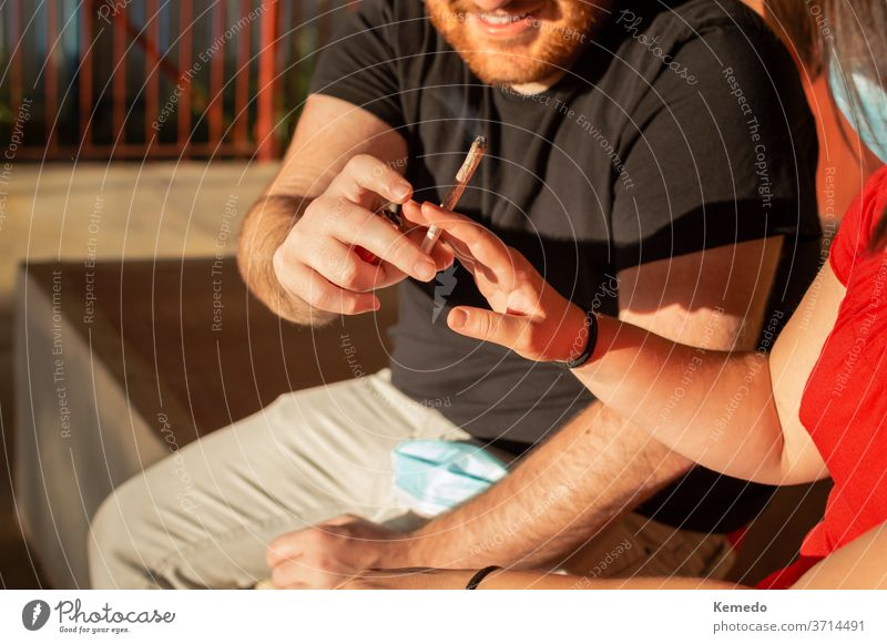 Young couple sharing a marijuana joint on the street during a sunset. pot cannabis smoke happy smile friends man boy guys outdoor hands give leisure beard