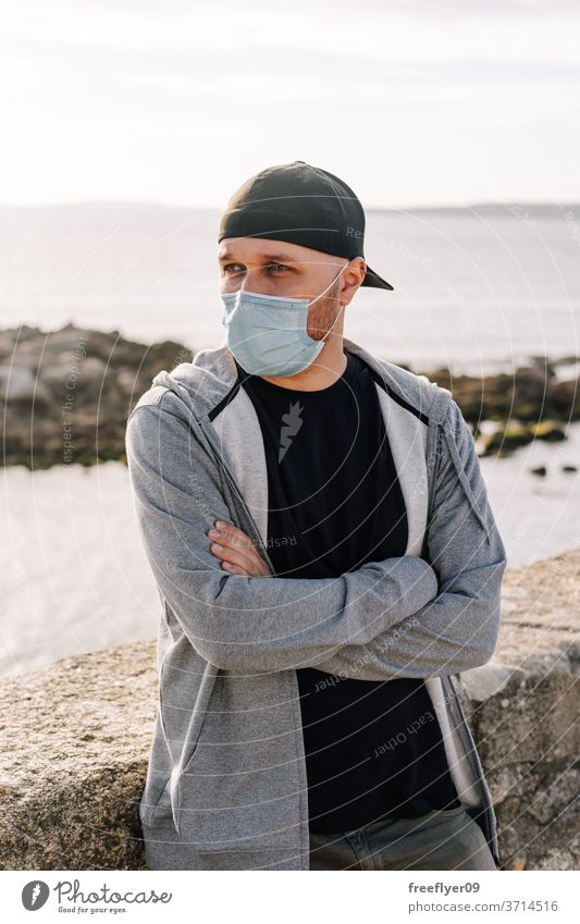 Tourist with a surgical mask near the ocean portrait man coast beach travel tourism tourist traveler pandemic coronavirus covid19 covid-19 sightseeing hat