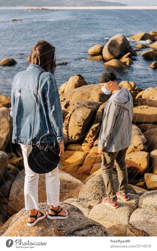 Couple of tourists near the ocean couple surgical mask coast beach travel tourism traveler pandemic coronavirus covid19 covid-19 sightseeing hat sweatshirt
