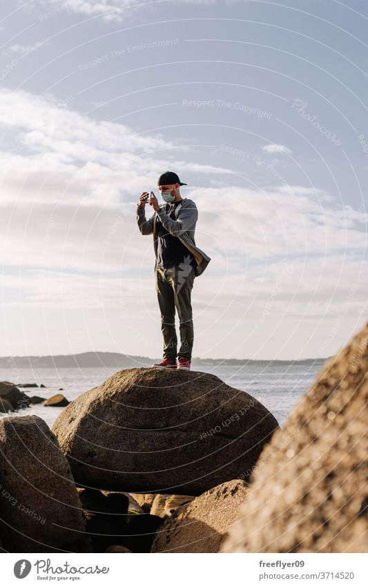 Tourist with a face mask taking photos with his smartphone tourist coast rock beach ocean portrait man surgical mask travel tourism traveler pandemic