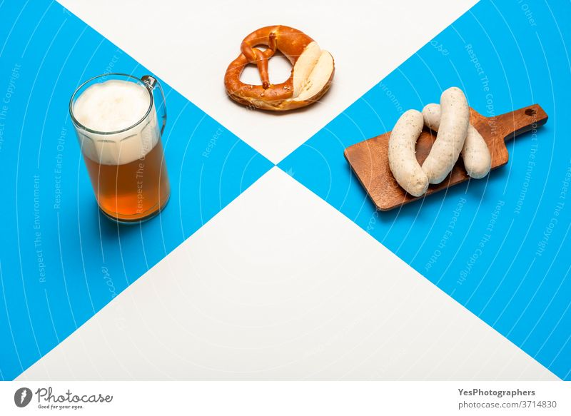 Oktoberfest table with a pint of beer, white sausage, and pretzel. Bavarian traditional meal Germany alcohol ale background bar bavarian beverage blue brew