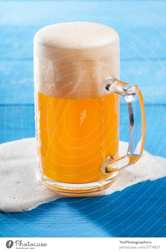 Pint of beer with spilled froth on blue table. German unfiltered beer Oktoberfest accident alcohol ale background bar bavarian beer foam beverage brew brewery