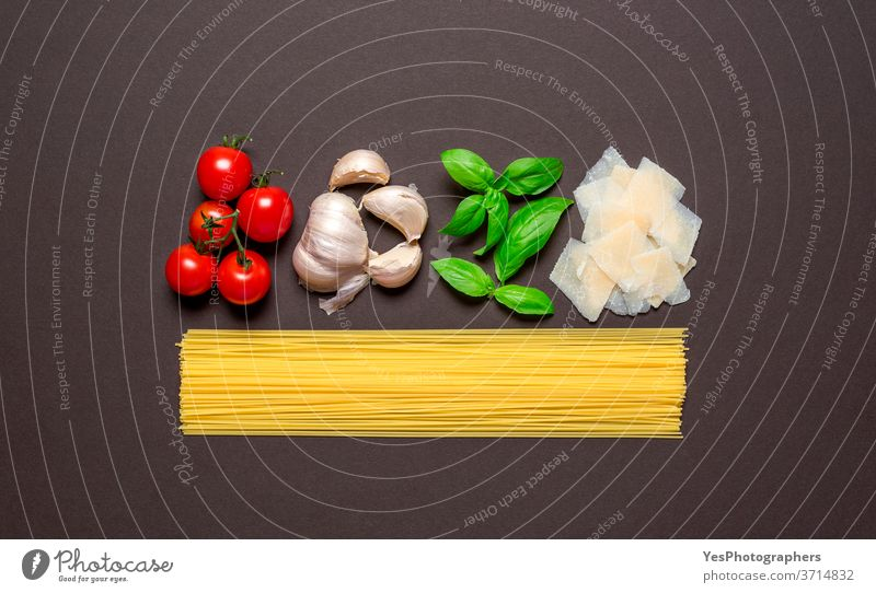 Spaghetti and the sauce ingredients, top view. Uncooked pasta isolated brown colored table. above view aligned background basil carbohydrate carbs cheese