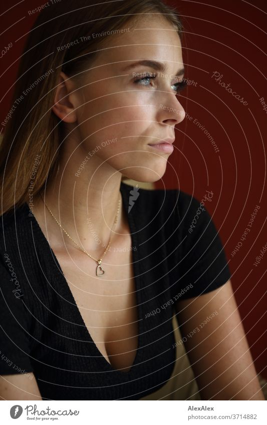 Lateral portrait of a young woman in front of a red wall Athletic Feminine empathy Emotions emotionally Central perspective Shallow depth of field