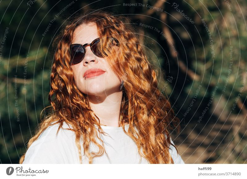 the young woman enjoys the morning sun in a relaxed manner Young woman portrait red lips red hair Red-haired Looking into the camera long hair 1 Sunglasses