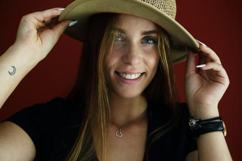 Direct portrait of a young woman in front of a red wall with a straw hat Athletic Feminine empathy Emotions emotionally Central perspective