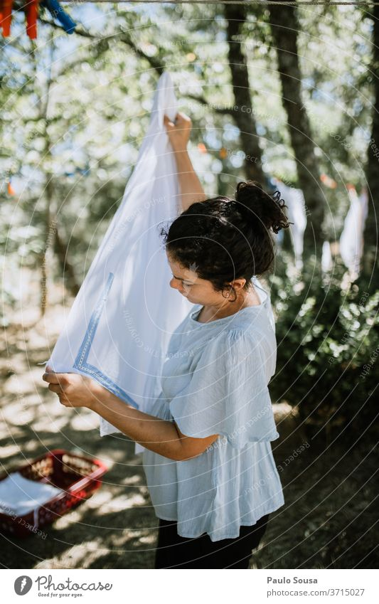 Woman hanging clothes on clothesline Clothing Clothesline Clothes peg Domestic domestic life Housewife housework Housekeeping Hang up Washing day Colour photo