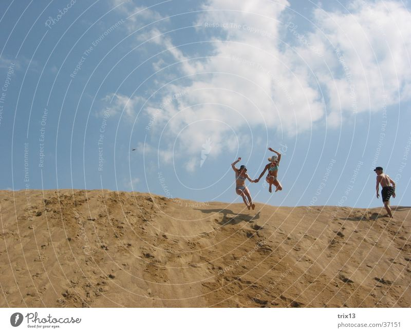 Human being Sky Blue Clouds Far-off places Jump Sand 2 Hill Hold hands