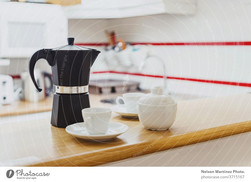Black coffee pot with white cups and a sugar bowl in the kitchen. Coffee maker in the kitchen. house serving hot drink warm weekend object style cosy nobody